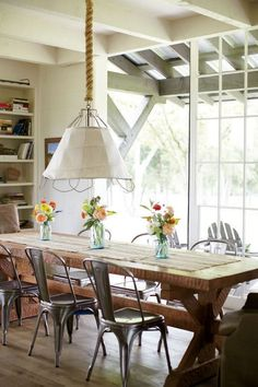 Coastal, rustic dining area with a large pendant lamp and farm table