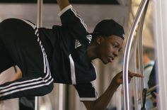 Young men perform daring aerial dances in a crowded New York City subway car.
