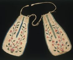 Pair of pockets, Britain  Pair of pockets, Britain, 1700-25. Museum no. T.697:BC-1913  Pair of pockets Britain 1700-25 Museum no. T.697:B  This pair of pockets is worked in coloured wool on linen, bound with wool tape, with linen ties. The embroidery designs on each are similar but not identical, suggesting both were hand-drawn. The motif of flowers growing from pots was a popular one in British embroidery from 1700 to 1750, and can be found on aprons and petticoats. The use of wool