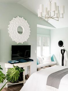 The master retreat starts with a serene background of sage green, but unexpected touches — like the black and white round rug on the wall — add tons of exciting personality.