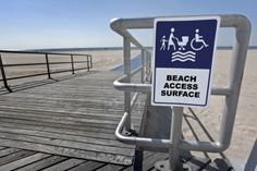 a wheelchair and a family  sign for easy access to the beach Stock Photo