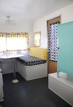 Vintage holiday camper trailer makeover, completely DIY. Remodel, restored with custom exterior auto paint, yellow, teal and black colour scheme, joel dewberry fabric, vinyl flooring, paneling, and antique steel pantry cabinet.