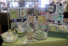 cards on a barbed wire rack, and a postcard holder, as well as in vintage milk glass and an old aqua cheese box