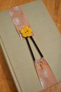 Ribbon Bookmark...looks simple enough: sew a hair band into the seams on one end of a ribbon and a button on the other.  Would like to try that!