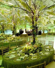 Great use of a tree in the middle of each table with floral sprays around it!