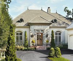 This home's grandeur relies on stately proportions in both massing and windows and a mix of warmly neutral materials:  http://www.bhg.com/home-improvement/door/exterior/european-doors/?socsrc=bhgpin092314countryfrenchinspired&page=2
