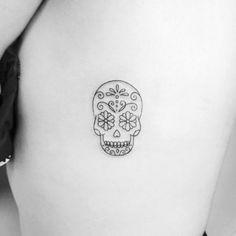 sugar skull [under left arm]