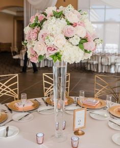 Tall clear vase centerpieces are great accents to round tables. Tall clear vase centerpieces are great accents to round tables. Wedding Floral: Weddings By Dzign Quince Centerpieces, Round Table Centerpieces, Purple Wedding Centerpieces, Wedding Vases, Wedding Table Decorations, Wedding Flower Arrangements, Round Tables, Floral Wedding, Wedding Flowers