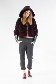 Giacca corta in pelliccia ecologica con cappuccio e manica 3 4 alla quale è  applicato un manicotto in ecopelle. La giacca è allacciata da una zip. f9cb68980ec