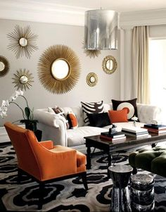 Chic black, white and beige geometric rug with orange chair and round gold mirrors. Arresting!