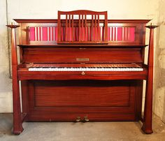 Arts and Crafts Bechstein upright pano with a mahogany case. Case features sculptural candlesticks and ornate brass hinges at Besbrode Pianos.. Designed by Walter Cave, English Architect and Interior Designer.