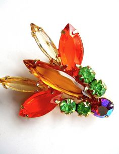 A JULIANA D&E bug brooch pin in multi color rhinestones and verified....vintage:  Gorgeous piece when looking at this colorful insect pin/brooch from Juliana D&E (verified in the Juliana Jewelry The Last Generation pg. 103). The rhinestones are all clear and vibrant, plus gold plating on the back. The wings show off vivid orange and light yellow rhinestones, while on the upper portion are peridot green rhinestones. At the tip is a chaton red AB rhinestone. This little gem shows off marquis…