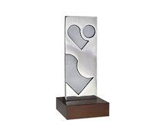Peça: bidimensional com relevos, 18cm de altura. Materiais disponíveis: alumínio (prata) ou bronze (dourado ou patinado). Base: madeira co...