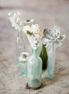 Pale succulents and soft white blooms in cloudy bottles