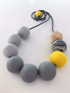 Chunky Monochrome & Yellow Colour Pop Polymer Clay Necklace with Dark Grey Cotton Cord  The round beads used to create this necklace have been hand-crafted from polymer clay. The swirly bead has been hand blended, and all beads have been rolled and shaped freehand, then baked and strung alongside a geometric wooden bead onto 2mm thick waxed cotton cord.  The cord length is approximately 72cm but this can be adjusted if you prefer a shorter length. The round beads approximately measure 25m...