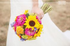 bouquet of pink zinnias, yellow sunflowers, daisies, and more