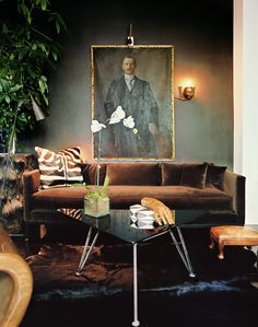 An oil painting above a brown couch and a triangular coffee table