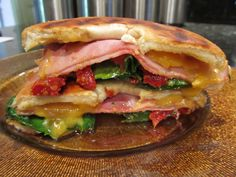 "SUN-DRIED TOMATO AND HAM GRILLED BAGEL ~ This sandwich was a result of another of my ""What's in the fridge?"" episodes. The jumping off point was a jar of sun-dried tomatoes and a bunch of baby spinach. And it only got better from there. This recipe serves one, but is easily doubled, quadrupled or whatever-ed is required to feed your bunch."