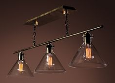 Add a Rustic look to your game room or Billiard table with this Edison lamp chandelier from Warehouse of Tiffany. Three Edison bulbs housed in cone-shaped conical clear glass shades while hanging from