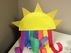 Sun rainbow made from half a paper plate and strips of paper.
