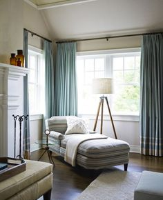 A corner perfect for curling up, done in stripes of blues and neutrals. A living room that wants to be lived in! Designed by Mendelson Group