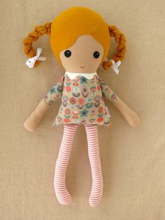 This is a handmade cloth doll measuring 18 inches. She is wearing a very retro floral print dress in gray, coral, and blue with coordinating coral