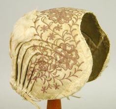 Bindmössa. Av vit atlas med tambursöm av grålila silke, 6 veck på var sida hophållna av ett linneband i dragsko. Fodrad med vit lärft. Vaddstoppning mellan stomme och atlas. Mycket trasig.