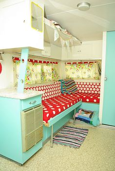 Renovated retro camper with an aqua, white, and red interior.