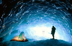 List of 20+ gorgeous ice caves to visit .  Man with tent in ice cave, Appa glacier, Pemberton Ice Field, British Columbia, Canada (© David Nunuk/Getty Image