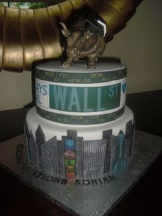 """Wall Street Bull Graduation Cake and Cupcakes!  This cake was created for a client who was celebrating their son's graduation from Brown University and new job at Barclays Capital in NYC. They wanted the cake to focus on the big news of his future in NYC as a financial analyst. The bottom tier was lemon cream and the top tier was french vanilla with bavarian cream filling. The Wall Street """"Charging Bull"""" was sculpted using rice crispie treats and fondant. 100% edible!"""