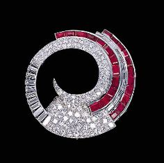 A RUBY AND DIAMOND CLIP BROOCH Designed as a pavé-set and baguette-cut diamond hoop with calibré-cut ruby trim, circa 1934