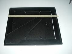 For picture frames with two holes, hang them evenly and easily by placing a single strip of masking tape over the back covering the two holes. Mark each end of the tape where the holes are located for hanging the frame. Take the tape off and place it on your wall. Make sure it is level then hammer a nail in at each pen mark.