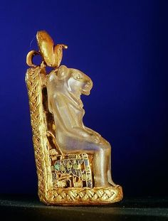 """quartz amulet (H.5,3cm) of the Goddess Bastet (wearing the Solar disk with the Uraeus) seated on a golden throne. From the """"House of Eternity"""" of 'Wen-djeba-en-djed', senior official of King Psusennes I, at Tanis; 1039-991 BCE. Now in the Cairo Museum"""