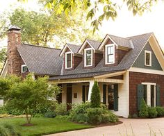 Cottage: Earthy Textures  This charming cottage-style home features a pleasing mix of earthy colors and textures. Dark-stained shakes blend nicely with the natural stone chimney while small doses of white provide contrast. Cutout patterned shutters painted dark green add color and detail.