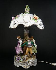 Plaue, Porzellanlampe, 'Figurenreigen' mit Lithophanien, 2-lichtig, über goldstaffiertem, mit plastischem Blüten verziertem Rocaillensockel 2 Paare um einen Baumstamm tanzend, Lampenschirm mit 4 Lithophanien 'Liebespaare' in Medaillonrahmen, Bekrönung un Form eines plastischen Blütenknaufes. 2 Hände restauriert, 3 Fingerspitzen bestoßen,  1  H 57cm, Dm 34cm.