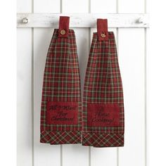 """The button loop kitchen towel comes with a working button loop. The body of the towel is 100% cotton red and green plaid with a red patch with the words """"All I want for Christmas"""" embroidered on one of the towels, and """"Is Home Cooking"""" on the other. The bottom has a plaid trim turned 45 degrees."""