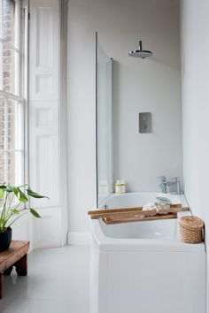 beautiful wooden details and green plants in the bathroom. The green plant in this bathroom makes it look so fresh and inviting.  Contemporary style - EcoCurve Showering Bath from Britton Bathrooms.