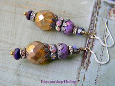 Candlelit Autumn Evenings  Artisan Earrings  You are cordially invited to dine by candlelight at the vineyard this Autumn. The smell of Autumn leaves dances on the warm breeze as we celebrate the harvest of rich purple grapes. In this pair of Victorian inspired earrings, we capture all the shades of the celebration. Rich shades of purple accent the candlelight glow of the focal beads, and beautiful rhinestones twinkle in the flickering light. A touch of green crowns each lovely earring…