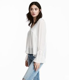 White. V-neck blouse in airy crêped fabric. Opening and tie at back of neck, lace yoke at back, seam and soft gathers below bust, and long sleeves with