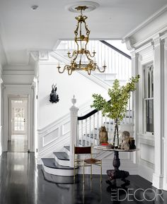 The entry's bronze chandelier is original to the house, as are the wood floors, which are stained ebony; the chair was found in a Brussels antiques market, and the walls are painted in Benjamin Moore's Decorators White. - ELLEDecor.com