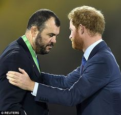 Prince Harry tried to console Australia's coach Michael Cheika as he leaves the podium after receiving his medal