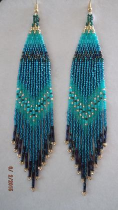 These Native Beaded Purple Earrings are custom made it Silver lined Turquoise, Transparent Turquoise, Turquoise, Dark Green, Peacock and Silver Lined Gold with Twisted Peacock Bugle Beads on them. They are about 7 in. long with Gold wires on them, can be changed to post or clips. It you have any Questions just ask. Thanks for looking.
