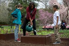 FILE - This April 15, 2015 file photo, first lady Michelle Obama waters a bed of vegetable seeds with students Nare Kande of the New York Botanical Gardens in the Bronx, N.Y., right, and Marley Santos of Foothill Elementary School in Boulder, Colo., left, during the seventh annual White House Kitchen Garden Planting on the South Lawn of the White House in Washington. The feel-good initiatives of first lady Michelle Obama have served as both inspiration and eight years of teaching moments for…