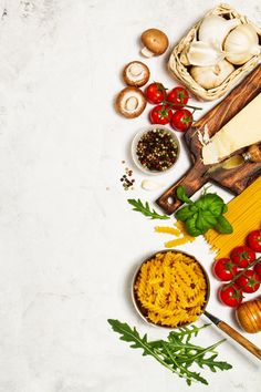 Raw pasta with tomatoes and spices with a cutting board with cheese Premium Photo
