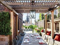 Architect John Murray, who collaborated on the renovation of the apartment with decorator Elissa Cullman, transformed the terrace into an urban oasis. Murray devised built-in lounge areas beneath retractable awnings, a pergola-topped dining space, and an outdoor kitchen, while landscape architect Edmund Hollander incorporated a profusion of willowy Russian sage and boxwoods in crisp ipe-wood planters.