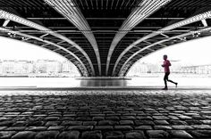 Under the Bridge - Girl in pink running under a bridge (Pont de l'Universite) in Lyon. It was bad, grey weather, there were no nice cityscapes to shoot. So I turned on the Black & White mode, and I thought this scene could be nice. The pink was an unexpected bonus.  I could not resist to post process it in this way. Hope you like it.