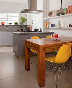 É o cooktop que toma conta da ilha em tom de cinza no projeto da SAO Arquitetura. A mesa de madeira maciça e cadeiras em amarelo descontraem o ambiente