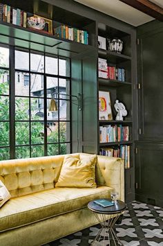Gold velvet tufted sofa in a window nook in a modern kitchen with built in bookshelves