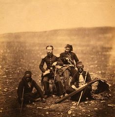 Crimean War Photographs by Roger Fenton, 1855 - Mr. Thompson of the Commissariat & attendants of Ismail Pacha, seated on a gabion, ront, surrounded by attendants of Ismail Pacha.