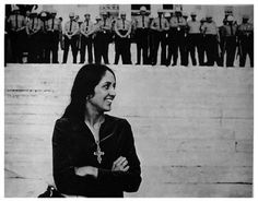 Joan Baez at the state capital in Montgomery, Alabama, with a line of Alabama state troopers, at the culmination of the March 26, 1965 Selma to Montgomery civil rights march led by Dr. Martin Luther King, Jr.   Baez was listening to Dr. King's speech while waiting her turn to perform before the crowd who had come from across the United States to support the Federal voting rights act and oppose segregation in schools and public places. photo by Steve Somerstein